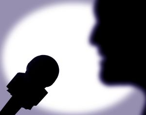 A person speaks into a microphone, 30 May 2001. Note: This image has been digit
