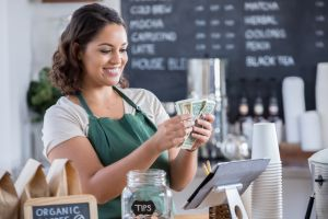 Young female barista counts money from tips jar
